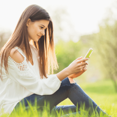 Girl on smartphone in Spring countryside